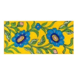 turquoise flower with green leaves on yellow tile