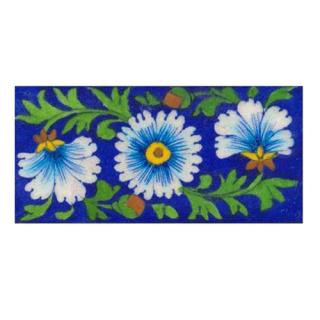 turquoise & white flower with green leaves on blue tile