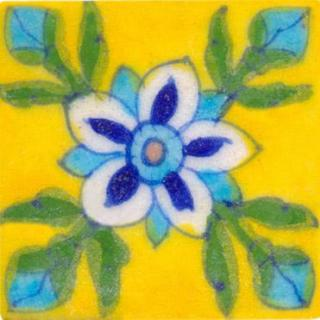 white, blue and turquoise flower wih green leaves on yellow tile