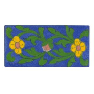 yellow flower with green leaves on blue tile